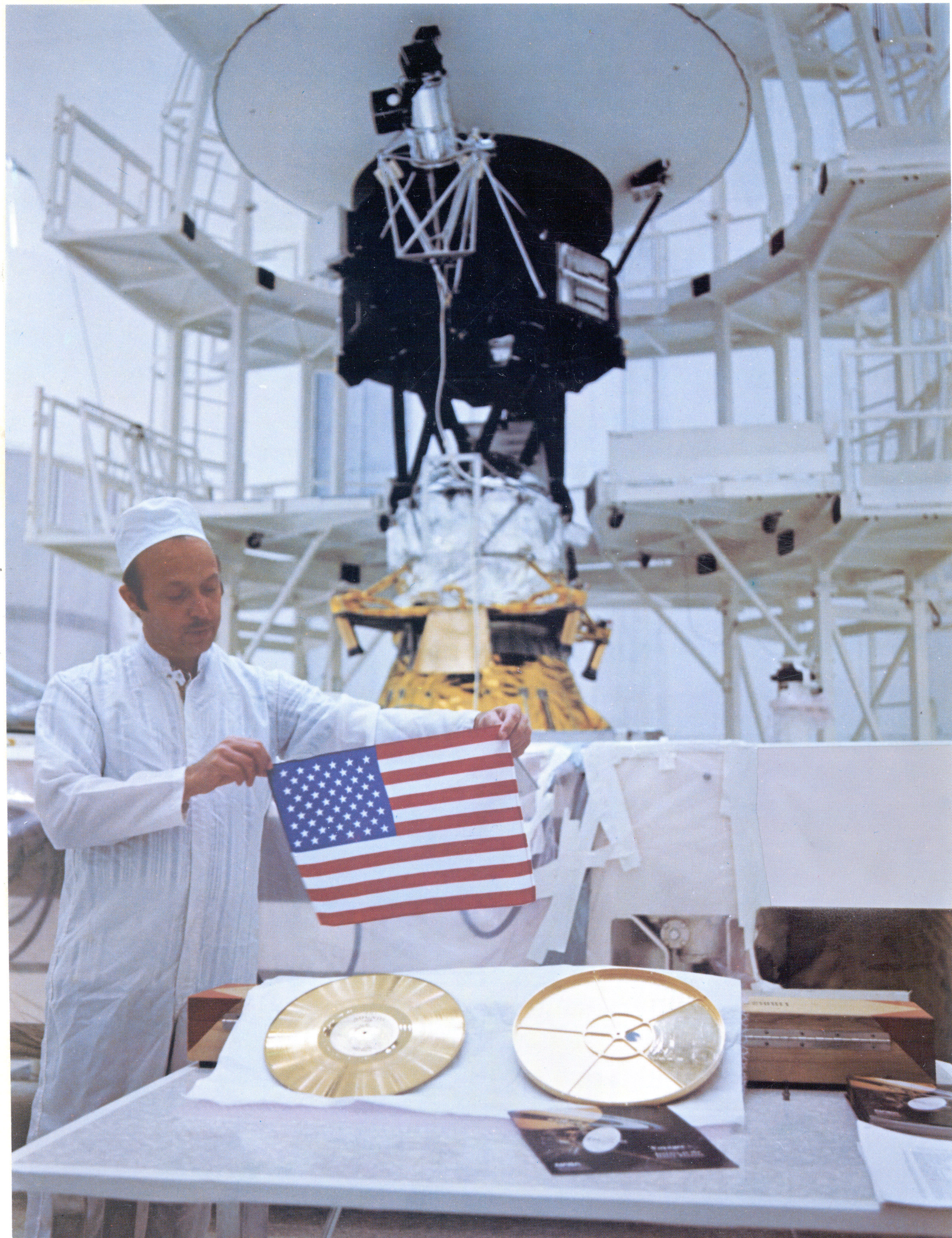 John Casani, August 4, 1977 — As NASA's two Voyager spacecraft travel out into deep space, they carry a small American flag and a Golden Record packed with pictures and sounds -- mementos of our home planet. This picture shows John Casani, Voyager project manager in 1977, holding a small Dacron flag that was folded and sewed into the thermal blankets of the Voyager spacecraft before they launched 36 years ago. Below him lie the Golden Record (left) and its cover (right). In the background stands Voyager 2 before it headed to the launch pad. The picture was taken at Cape Canaveral, Florida, on August 4, 1977.