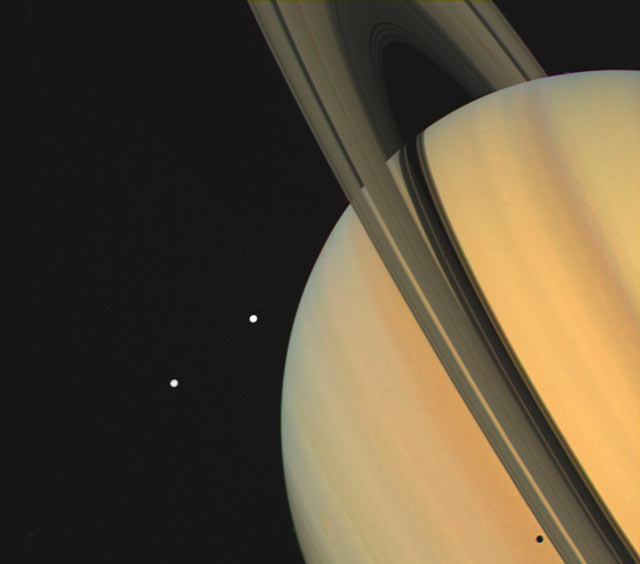 Saturn. Moons Tethys. Dione. Shadows, rings and moons on Saturn. Photo Nov. 3. 1980. Range 13 million km.