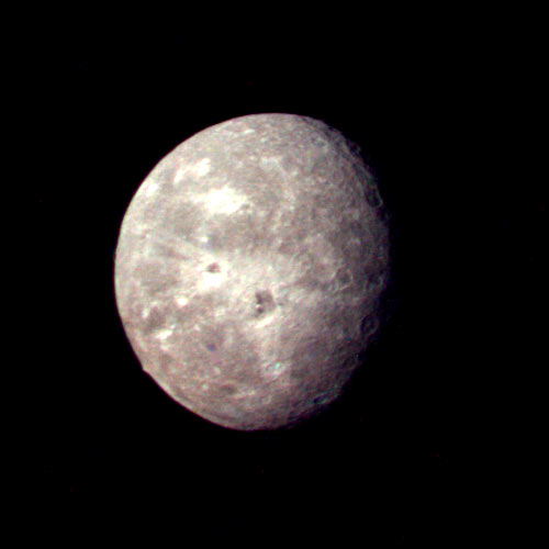 Best image of Oberon shows cratering and large peak on moon's lower limb. January 24, 1986. Range 410,000 miles.