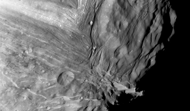 Miranda displays rugged, high-elevation terrain (right), lower, grooved terrain and large crater (lower left) 15 miles across. January 24, 1986. Range, 22,000 miles.