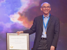 Ed Stone, the project scientist of NASA's Voyager mission, stands with his NASA Distinguished Public Service Medal and accompanying certificate. He received the award on the talk show The Colbert Report on Dec. 3, 2013.