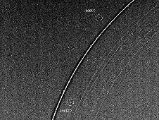"Voyager 2 has discovered two ""shepherd"" satellites associated with the rings of Uranus. The two moons -- designated 1986U7 and 1986U8 -- are seen here on either side of the bright epsilon ring; all nine of the known Uranian rings are visible. Image credit: NASA/JPL"