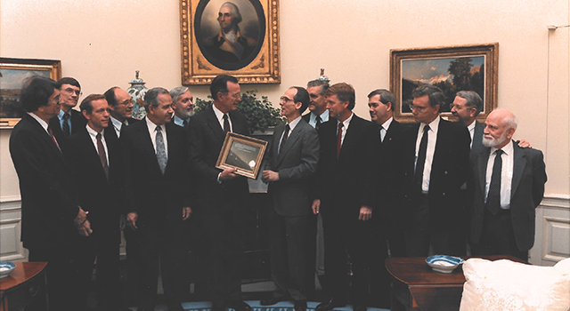 "Voyager Project Scientist Ed Stone and other mission team members gave a framed copy of an iconic Voyager 1 solar system image that includes Earth as a ""Pale Blue Dot"" to President George H.W. Bush on June 7, 1990. The presentation was made at the White House in the Oval Office. Pictured L-R: Stamatios K. (tom) Krimgis, Barney J Conrath, Norman R. Haynes, Richard P. Laeser, George P. Textor, Lennard A. Fisk, Pres. George H.W. Bush, Edward C. Stone, Raymond L. Heacock, Earle T. Huckins, Esker K. (Ek) Davis, Adm. Richard H. Truly, Rudolf A. Hanal."