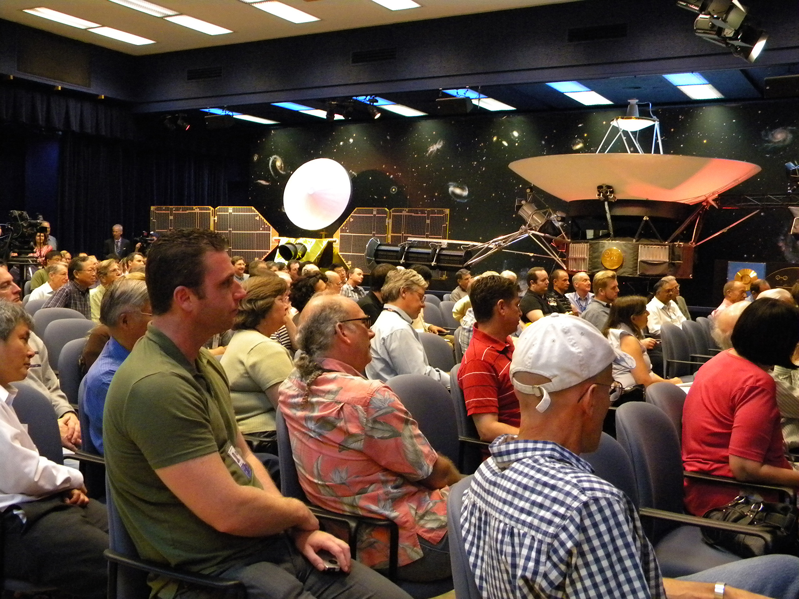 As part of a celebration of 35 years of flight for NASA's Voyager spacecraft, a crowd of engineers and scientists at NASA's Jet Propulsion Laboratory in Pasadena, Calif., gather at von Karman auditorium to listen to insider stories about Voyager. At the top right of the picture is a full-size model of Voyager. Image credit: NASA/JPL-Caltech